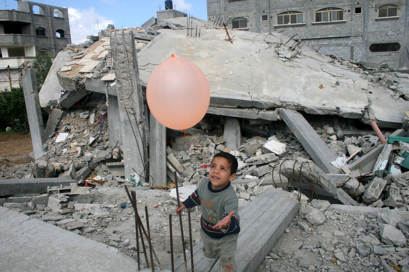 Boy plays with balloon amongst rubble of destroyed building