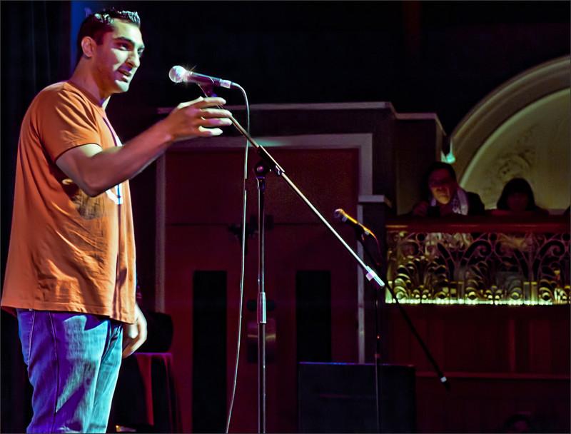 Remi Kanazi performing on stage