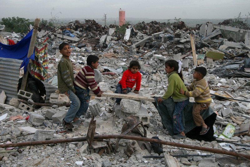 Children play on improvised see-saw amidst rubble of destroyed buildings