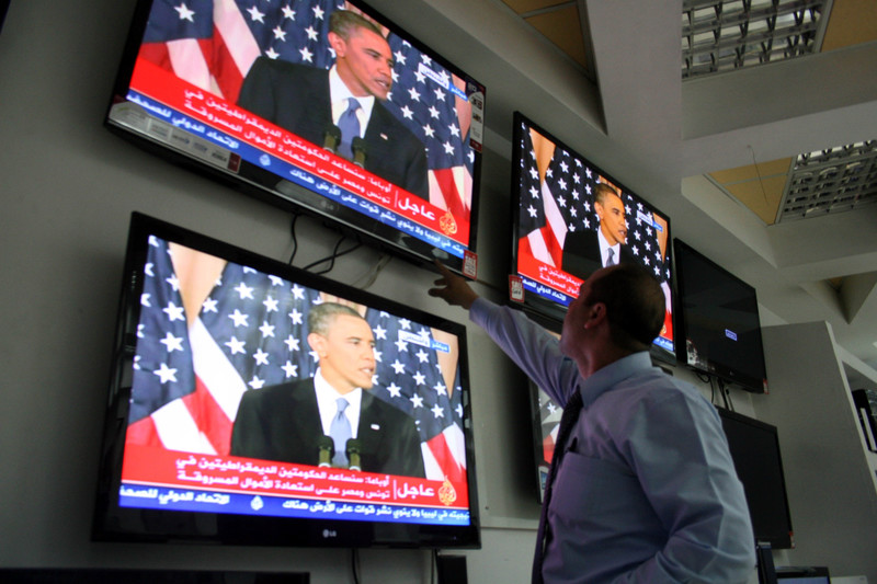 Man points at television screens showing Barack Obama