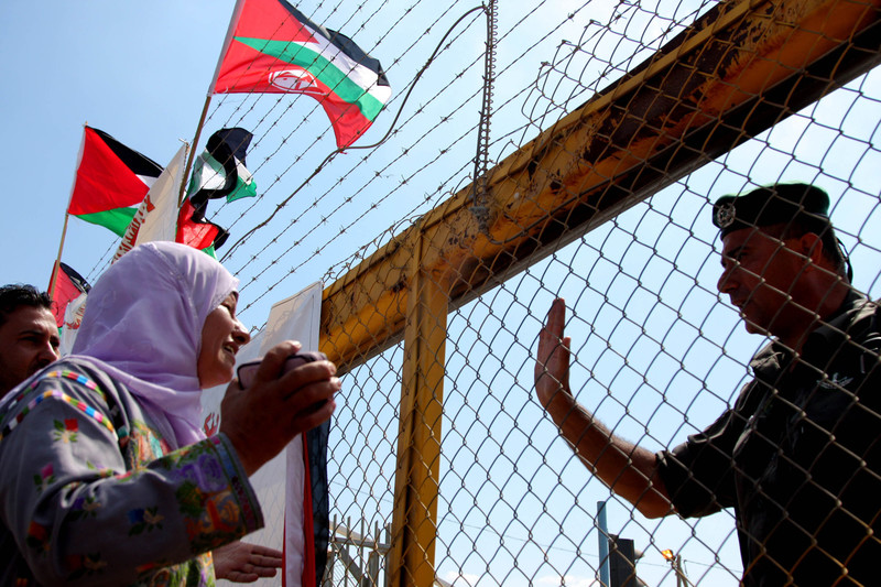 Woman holds sign in front of Israeli prison gates