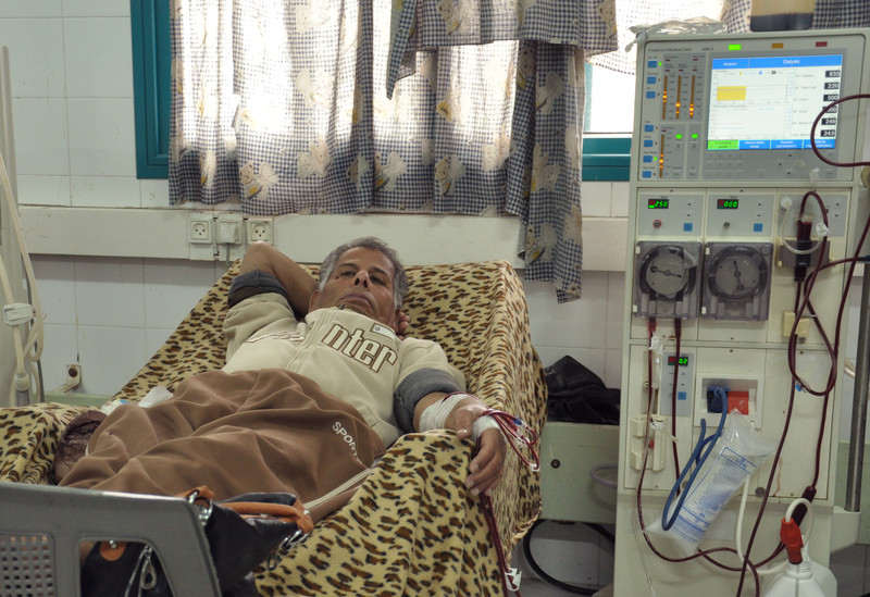 Man lying in bed is hooked up to dialysis machine