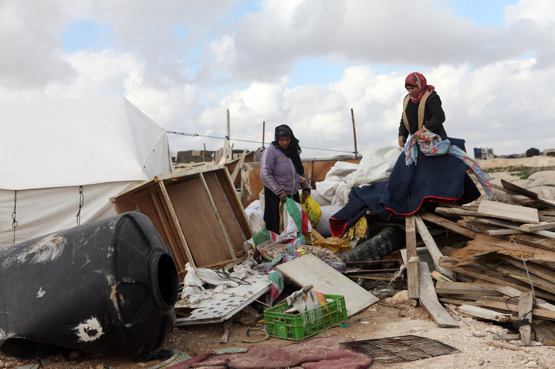 Women sort through rubble of destroyed homes