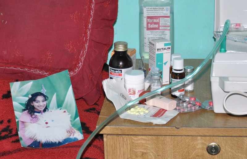 A portrait photo of Haneen lays on her bed while medicines sit on table next to bed