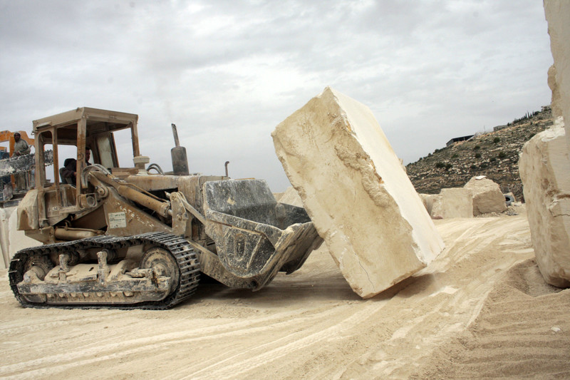 A construction vehicle moves a large block of concrete
