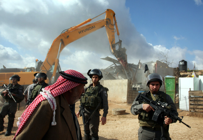 Bedouin man walks in front of Israeli soldiers guarding Hyundai equipment destroying structures