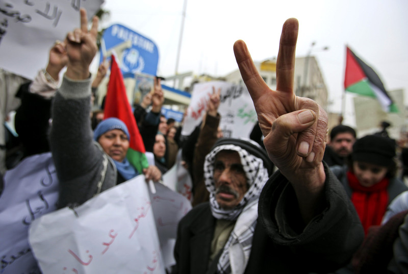 "Palestinians flash ""v"" for victory symbol at Khader Adnan rally"