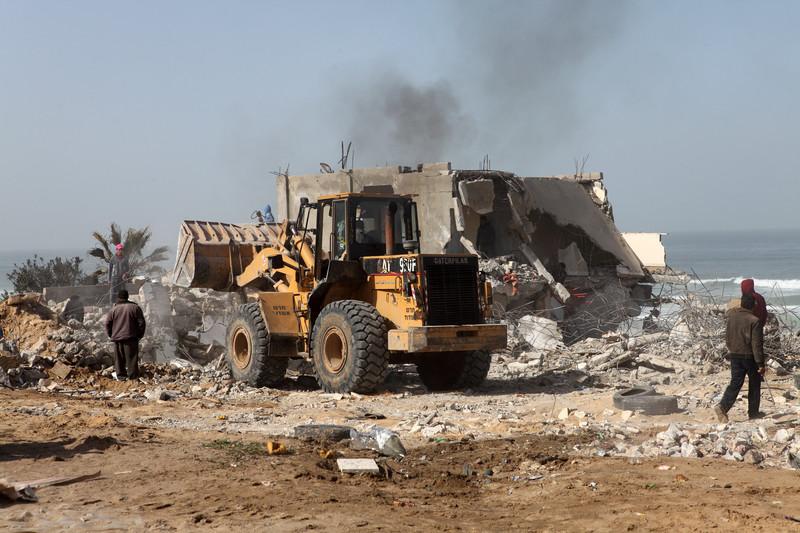 Earth-moving machine bulldozes homes along coast