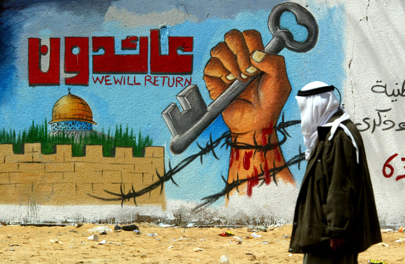 "Man walks by mural of fist holding key reading ""We will return"" in Arabic and English"