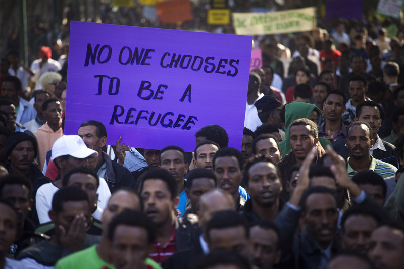 "Sign stating ""No one chooses to be a refugee"" displayed at protest of asylum-seekers"