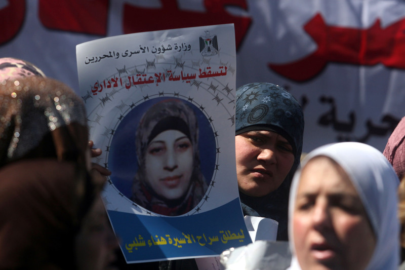 Woman displays poster of Hana al-Shalabi at rally