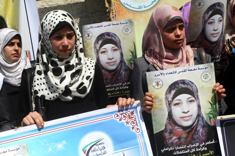 Young women hold posters in solidarity with Hana al-Shalabi