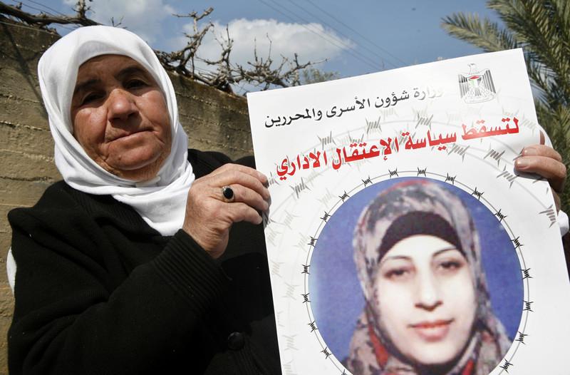 Badia al-Shalabi displays poster of her daughter