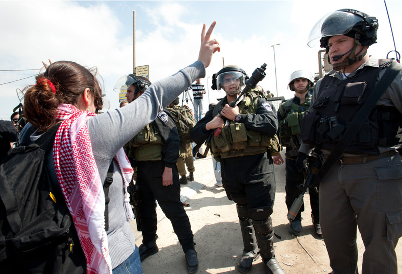 "Woman makes ""v"" for victory hand gesture in front of Israeli soldiers"
