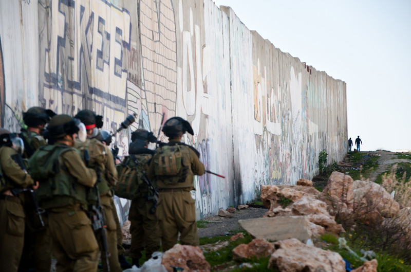Heavily armed Israeli soldiers in front of grafittied concrete wall