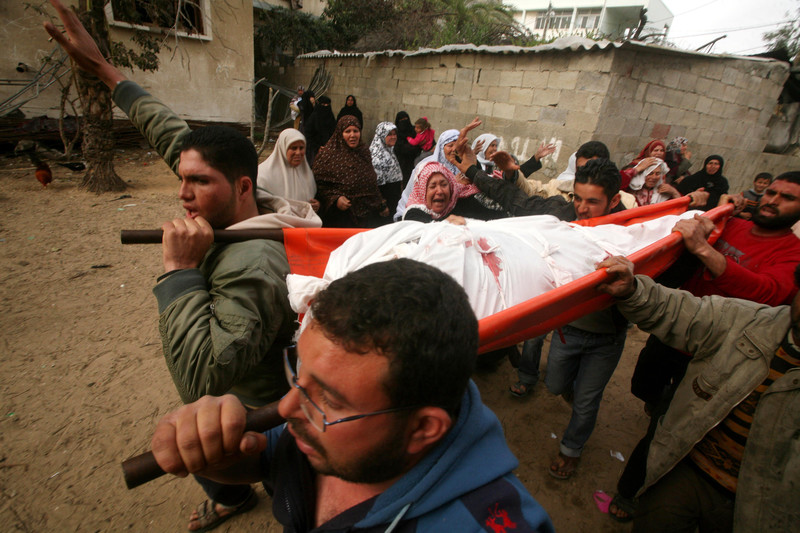 Women mourners stand to side as men carry body of killed Gaza man