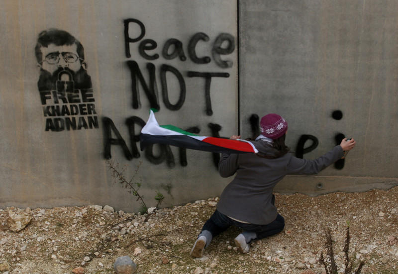 "Someone with back turned to camera spray paints ""Peace not apartheid"" and Khader Adnan stencil on West Bank wall"