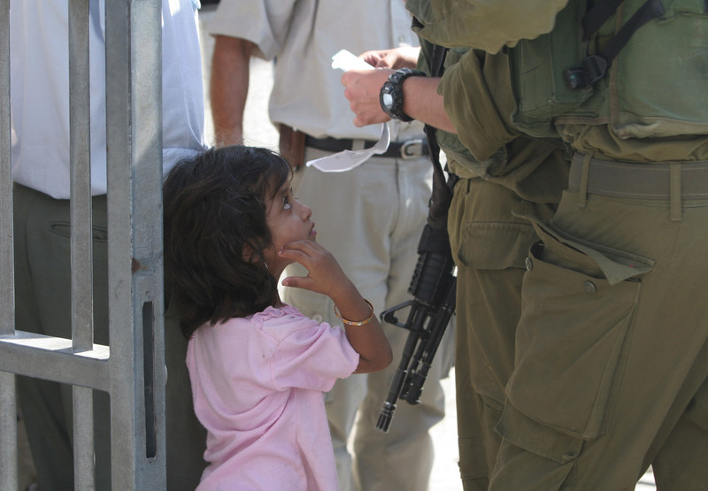 Israeli soldiers examine ID of young girl