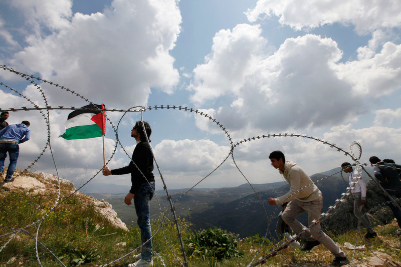 Young men and barbed wire in foreground with landscape of northern Palestine in background