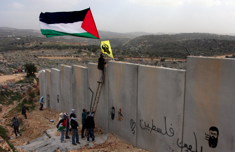 Protesters use ladder to fly flags over West Bank wall