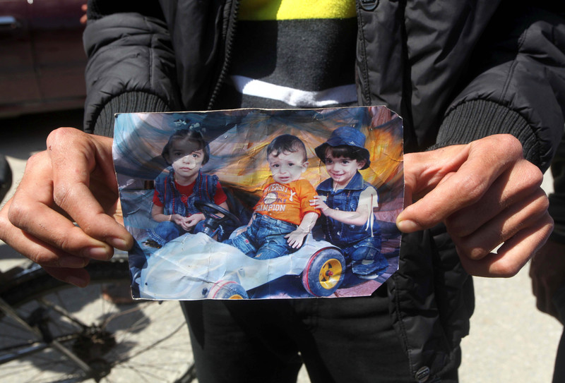 Man displays worn portrait photograph of three small children killed in fire