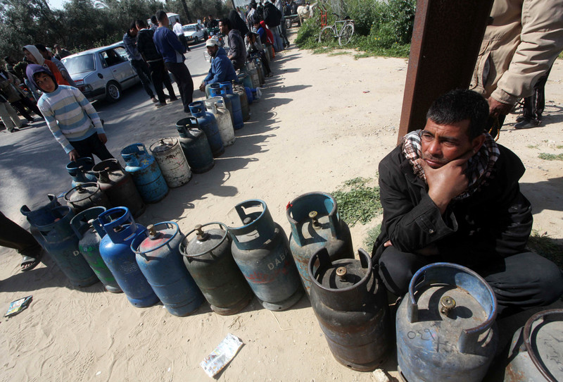 Man sits next to queue of gas canisters