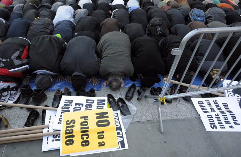 Men pray near picket signs protesting the targeting of Muslims