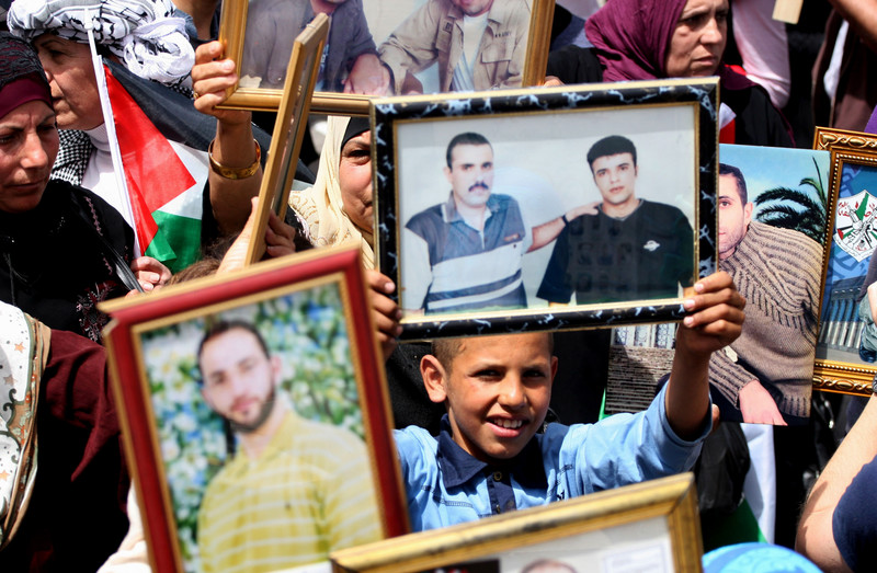 Demonstrators display portraits of loved ones in Israeli prisons