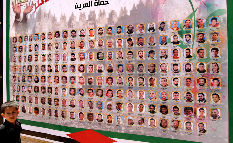 Boy stands in front of poster featuring faces of hunger-striking prisoners