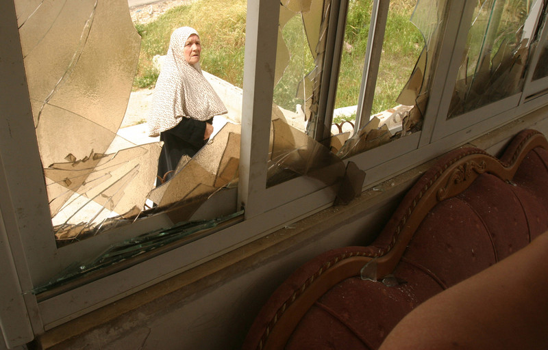 Woman is seen through broken window