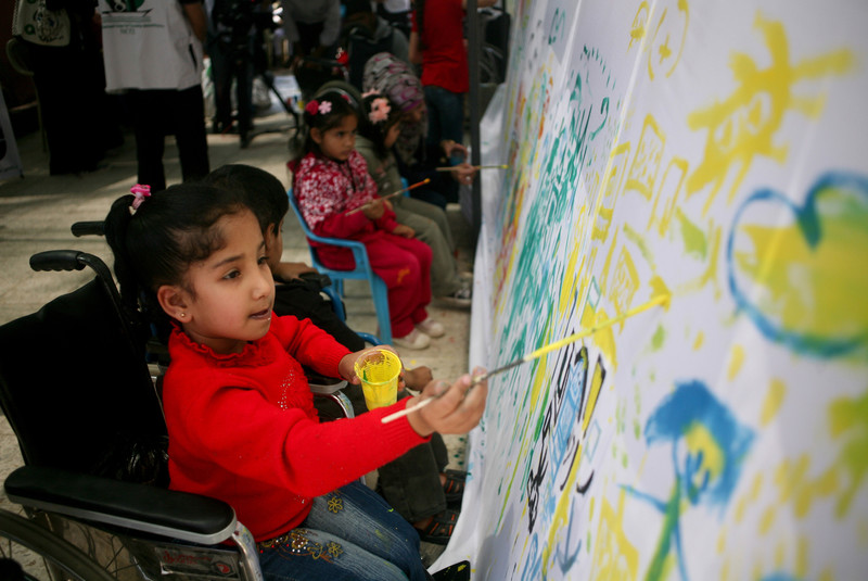 Girl using wheelchair paints on a mural