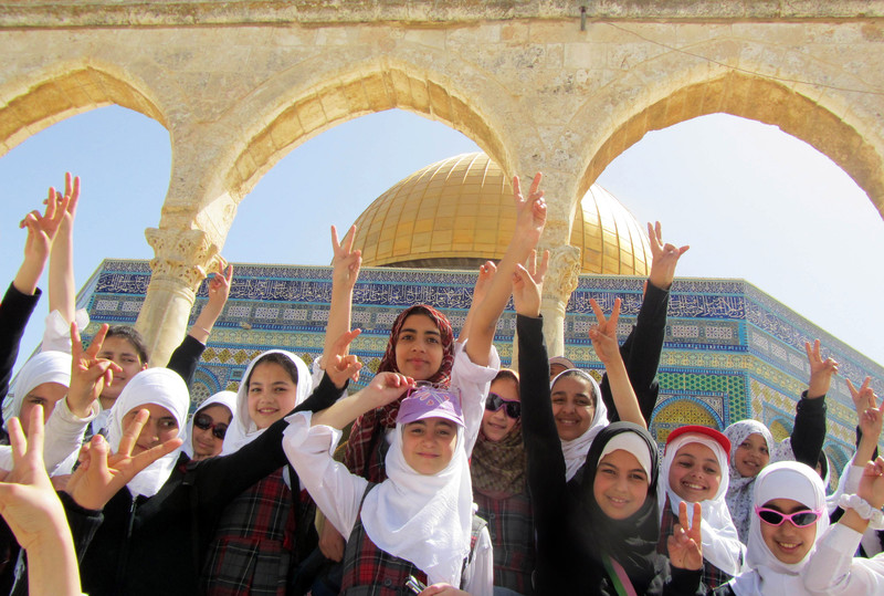 "Girls smile and raise ""victory"" hand gesture in front of Dome of the Rock"