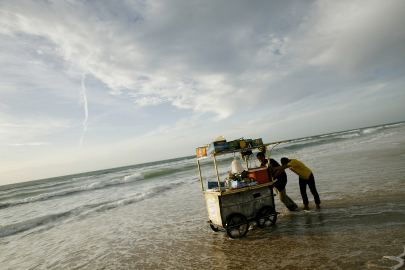 Two people push cart on the shore of the sea