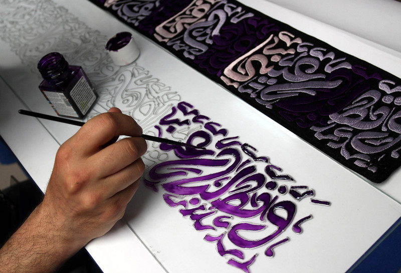 Man works on calligraphic art