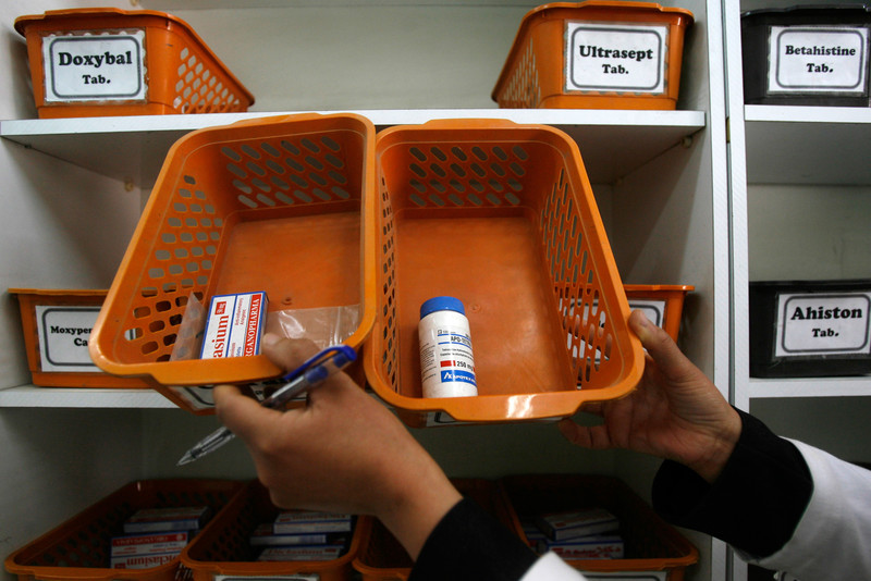 Pharmacist displays empty stocks of medicine