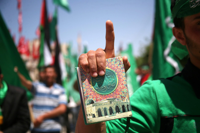 Demonstrator holds Quran and points toward sky