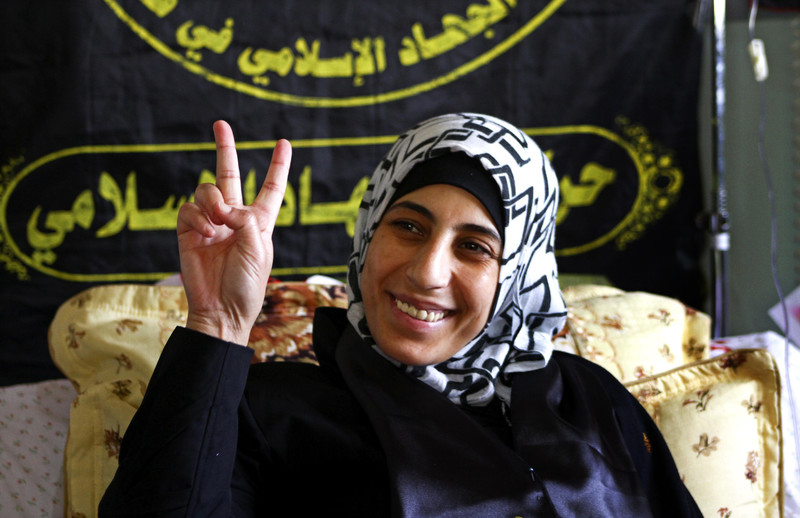 "Hana al-Shalabi makes ""victory"" hand gesture while resting on bed"