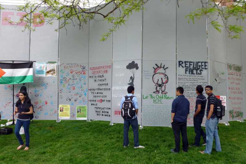 Students look at mock wall displaying messages about Palestine