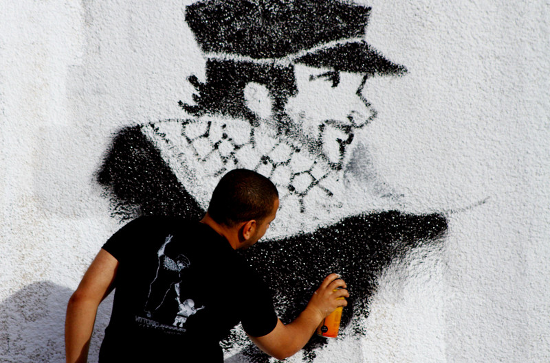 Man spray-paints portrait of Vittorio Arrigoni
