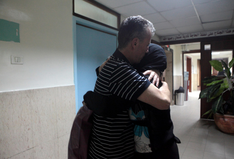 Bassem Tamimi hugs his wife in hallway