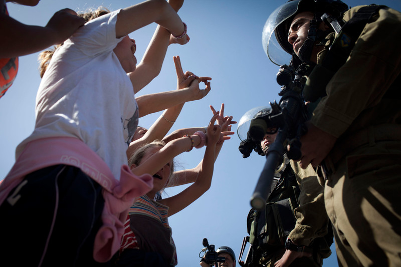 Girls shout and display victory hand gesture to armed Israeli soldiers