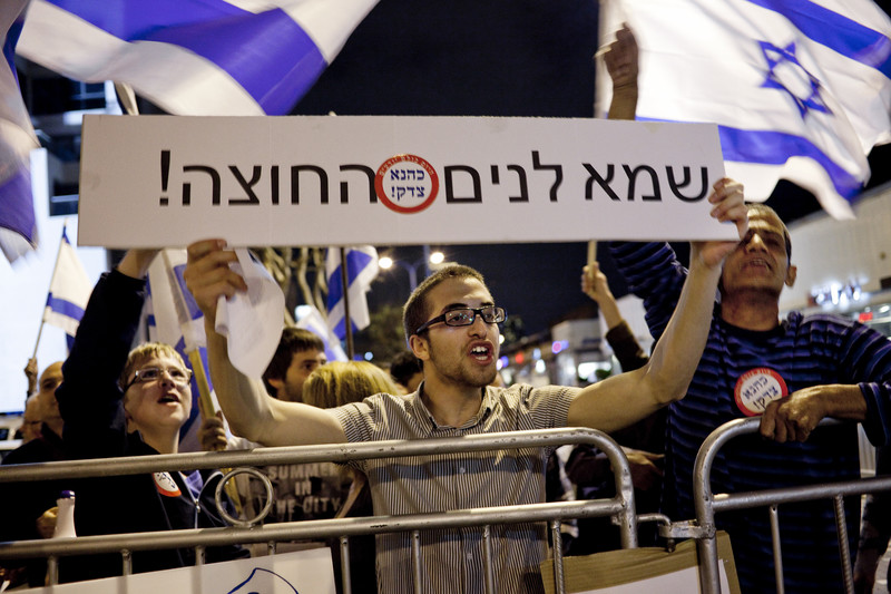 Israelis wave state flag and display signs with ultra-nationalist messaging