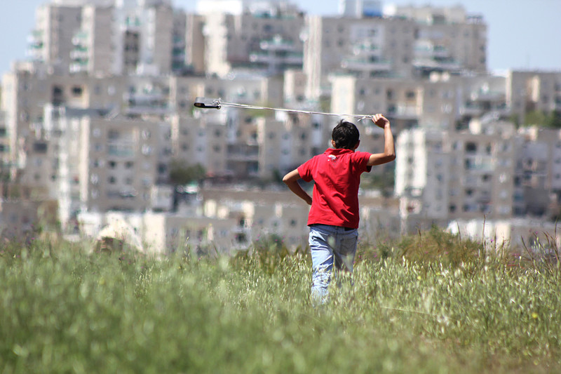 Boy with slingshot in field with settlement mid-rises in background
