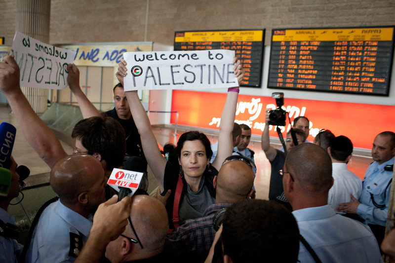 "Activists display signs reading ""Welcome to Palestine,"" surrounded by media"