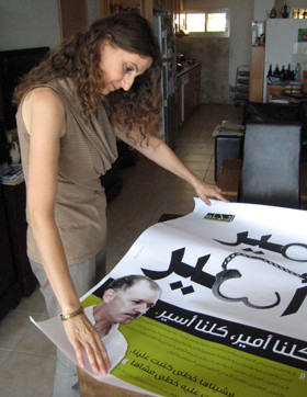 Janan Abdu looks at poster of jailed husband Ameer Makhoul