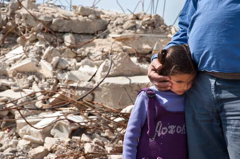 Close-up of man cradling head of girl, with rubble of destroyed home in background