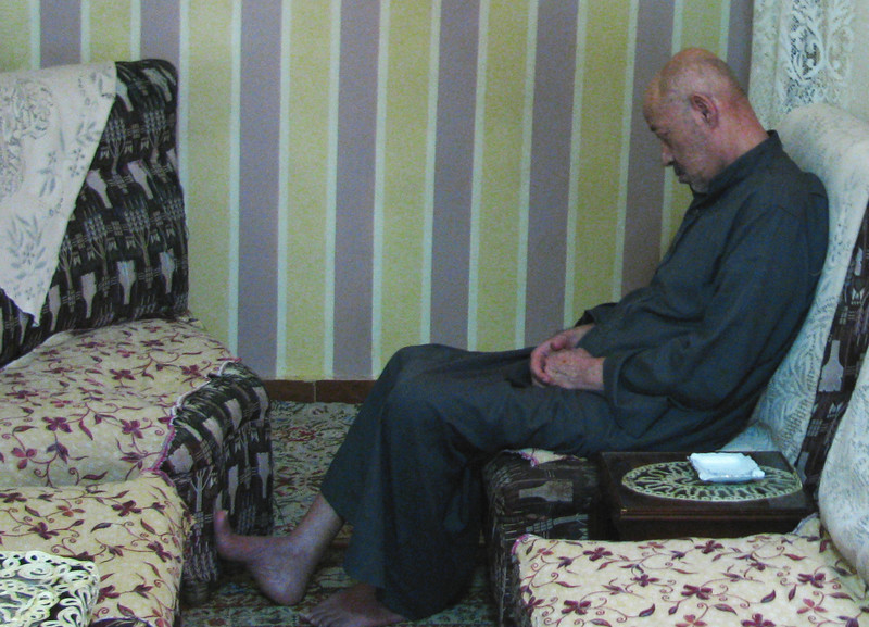 Forlorn-looking man sits in living room