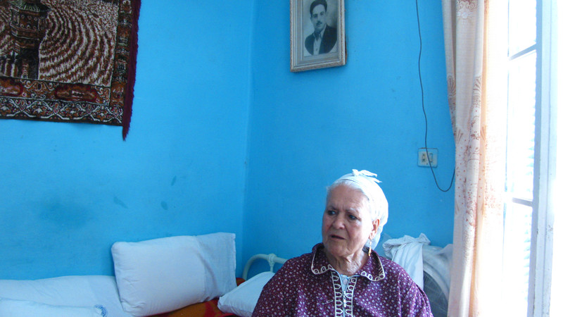 Elderly woman sits in brightly-colored room