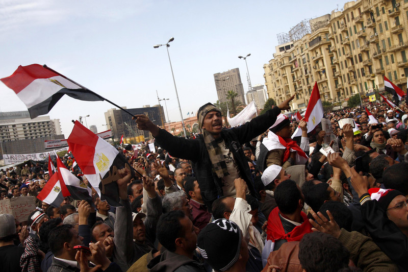 Man in crowd waves Egyptian flag