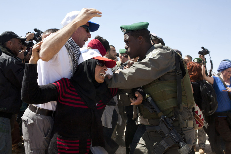 Woman attempts to stop a soldier from arresting man